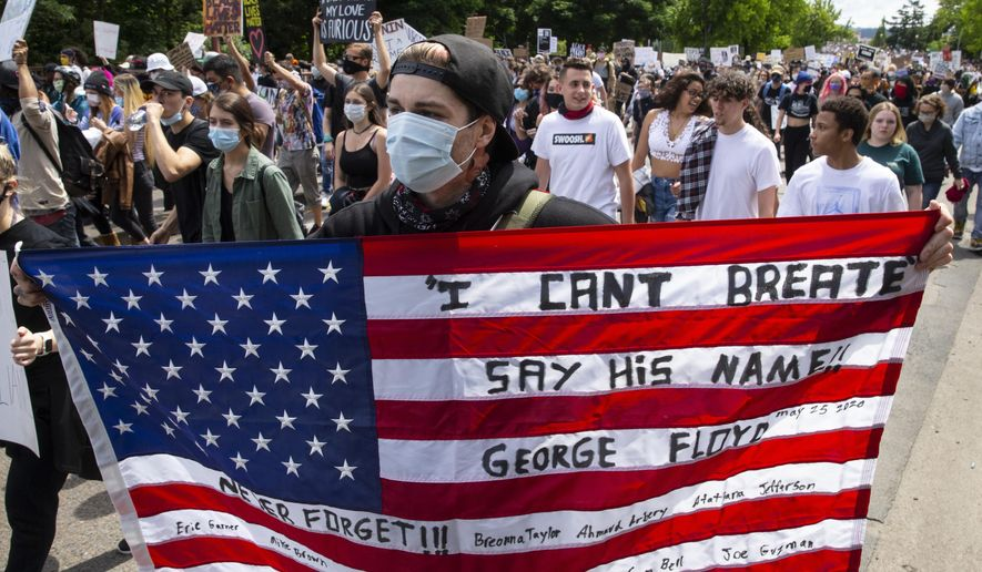 A person holds a U.S. flag with messages on it, during a Black Lives Matter March in Eugene, Ore., Sunday, May 31, 2020, over the deaths of George Floyd and others. (Chris Pietsch/The Register-Guard via AP)