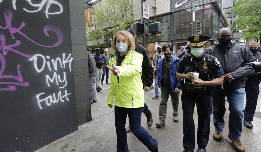 Seattle Mayor Jenny Durkan, left, surveys downtown Seattle with Police Chief Carmen Best on Sunday, May 31, 2020, following protests the night before over the death of George Floyd, a black man who was in police custody in Minneapolis. On Sunday morning, hundreds of people of all ages turned out in downtown Seattle to help clean up the damage, sweeping up broken glass and cleaning off graffiti. (AP Photo/Elaine Thompson)