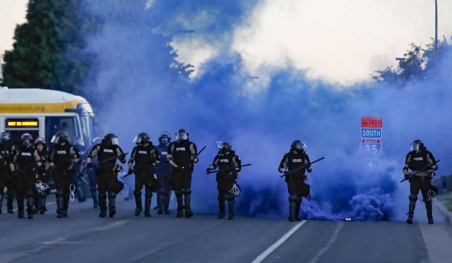 Police in riot gear prepare to advance on protesters, Saturday, May 30, 2020, in Minneapolis. Protests continued following the death of George Floyd, who died after being restrained by Minneapolis police officers on Memorial Day. (AP Photo/John Minchillo)