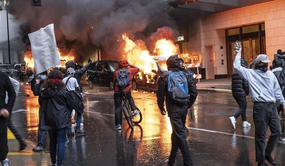 People set fire to vehicles during a protest, Saturday, May 30, 12020 in Seattle. Protests were held throughout the country over the death of George Floyd, a black man who died after being restrained by Minneapolis police officers on May 25. (Dean Rutz/The Seattle Times via AP)
