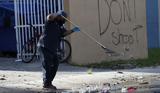 """A City of Miami employee cleans up debris from the street next to graffiti reading """"Don't Shoot"""" in the aftermath of protests over the death of George Floyd, Sunday, May 31, 2020, in Miami. Protests were held throughout the country over the death of Floyd, a black man who died after being restrained by Minneapolis police officers on May 25. (AP Photo/Lynne Sladky)"""