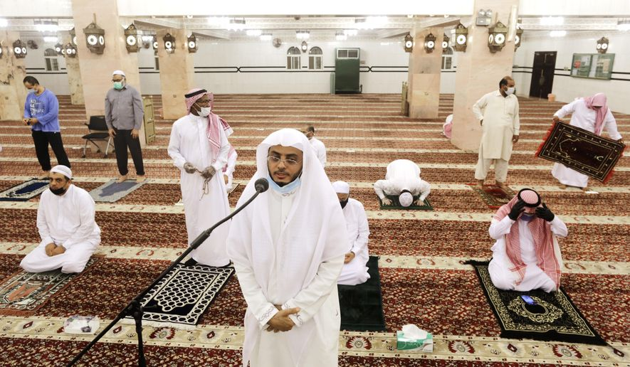 Saudi cleric Hammoud Al-Labban recites the call to prayers as worshippers wearing face masks and observing social distancing guidelines to protect against the new coronavirus, attend dawn prayers at al-Mirabi Mosque in Jiddah, Saudi Arabia, Sunday, May 31, 2020. The Ministry of Islamic Affairs said mosques will open to the public for prayers from May 31 until June 20, except in Mecca, with precautionary measures and instructions. (AP Photo/Amr Nabil)