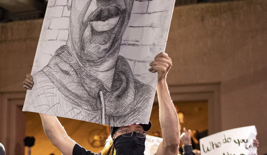A demonstrator holds up a drawing depicting George Floyd in Albuquerque, N.M., Sunday, May 31, 2020. Protests were held in U.S. cities over the death of Floyd, a black man who died after being restrained by Minneapolis police officers on May 25. (AP Photo/Andres Leighton)