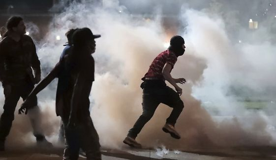 Protesters throw smoke bombs back at the Shelby County Sheriff's deputies Sunday, May 31, 2020, during a protest over the death of George Floyd on May 25. (Jim Weber/Daily Memphian via AP)