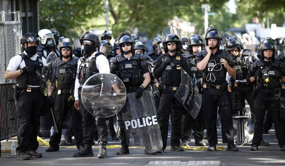 U.S. Secret Service police wait in Lafayette Park as demonstrators gather to protest the death of George Floyd, Monday, June 1, 2020, near the White House in Washington. Floyd died after being restrained by Minneapolis police officers. (AP Photo/Alex Brandon)