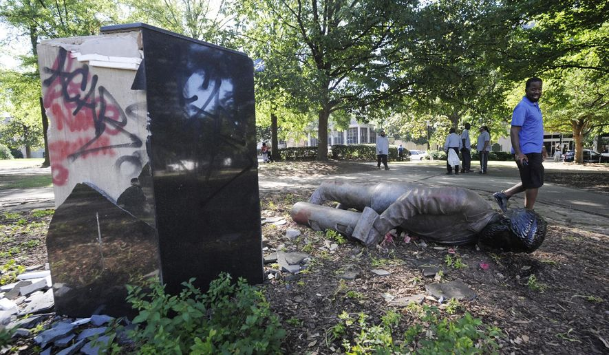 An unidentified man walks past a toppled statue of Charles Linn, a city founder who was in the Confederate Navy, in Birmingham, Ala., on Monday, June 1, 2020, following a night of unrest. People shattered windows, set fires and damaged monuments in a downtown park after a protest against the death of George Floyd. Floyd died after being restrained by Minneapolis police officers on May 25. (AP Photo/Jay Reeves)