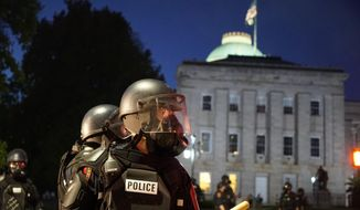 Police in riot gear protect the old state capitol building in Raleigh, N.C., on Sunday, May 31, 2020. It was the second day of protests in the North Carolina capital following the death of Minnesotan George Floyd while in police custody. (AP Photo/Allen G. Breed)