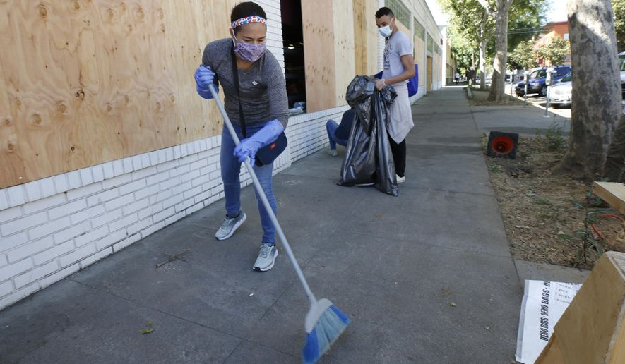 Volunteer Jennifer Kistler-McCoy sweeps up glass from shattered windows at a store Monday, June 1, 2020, that was damaged Sunday in Sacramento, Calif. Nearly two-thirds of the properties in Sacramento's downtown business district were damaged over the weekend following three consecutive days of protests over the killing of George Floyd, a black man who died after being restrained by Minneapolis police officers on May 25. (AP Photo/Rich Pedroncelli)