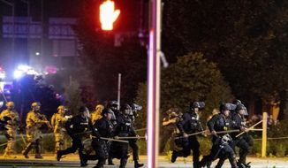Police and Kentucky National Guard troops chase protesters as they flee toward a fence Sunday, May 31, 2020, in a parking lot at the corner of East Broadway and South Brook Street in downtown Louisville, Kentucky. (Max Gersh/The Courier Journal via AP)