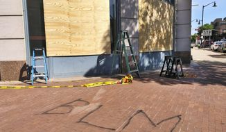 Workers boarded up the windows on a building in downtown Trenton, NJ, that houses businesses as well as state government offices, Monday June 1, 2020. Calling to mind the Black Lives Matter movement, someone spray painted BLM on the sidewalk Sunday night in reaction to George Floyd's death while in police custody on May 25 in Minneapolis. (AP Photo/Mike Catalini)