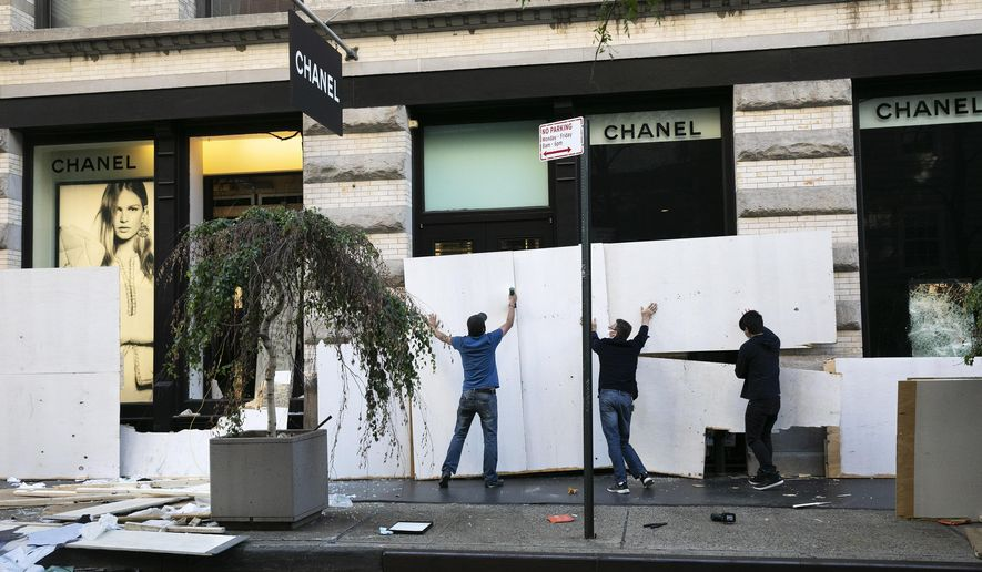 Workers board up the windows of a Chanel store Monday, June 1, 2020, following protests in the SoHo neighborhood of New York. Protests were held throughout the country over the death of George Floyd, a black man who died after being restrained by Minneapolis police officers on May 25.  (AP Photo/Mark Lennihan)