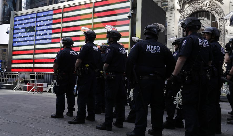 Police officers in riot gear stand by in Times Square during a protest in Manhattan in New York, Monday, June 1, 2020. New York City imposed an 11 p.m. curfew Monday as the nation's biggest city tried to head off another night of destruction erupting amid protests over George Floyd's death. (AP Photo/Seth Wenig)