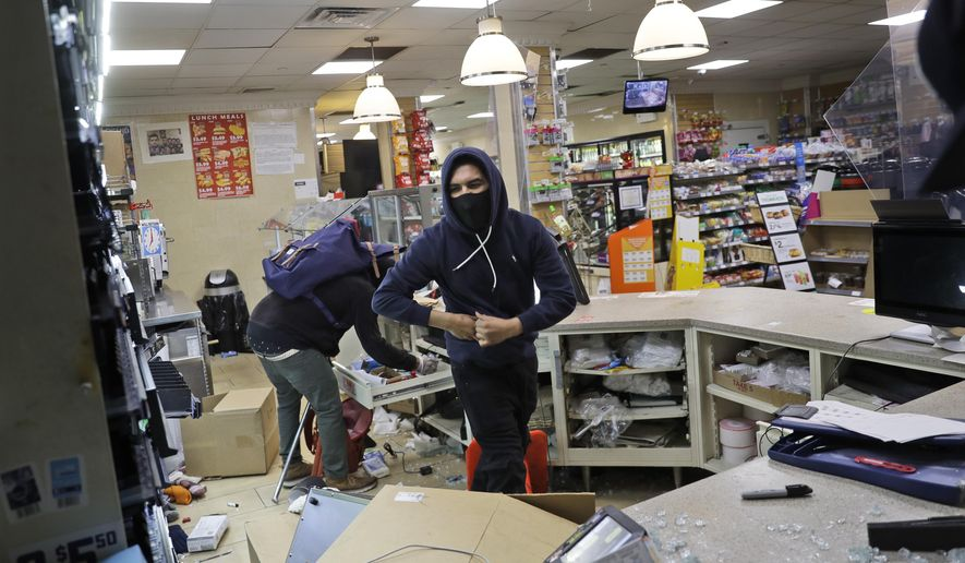 People look through a 7-Eleven store after they entered through a smashed window in New York, Sunday, May 31, 2020. Demonstrators took to the streets of New York to protest the death of George Floyd, who died May 25 after he was pinned at the neck by a Minneapolis police officer. (AP Photo/Seth Wenig)