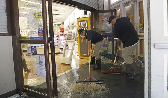 Mark Meddings, left, and Alan Sargent, right, push water out of a Rite Aid store Monday, June 1, 2020, in Sacramento, Calif. A fire was started in the store that was vandalized over the weekend by people protesting the death of George Floyd. Nearly two-thirds of the properties in Sacramento's downtown business district was damaged over the weekend following three consecutive days of protests over the killing of Floyd, a black man who died after being restrained by Minneapolis police officers Memorial Day. (AP Photo/Rich Pedroncelli)