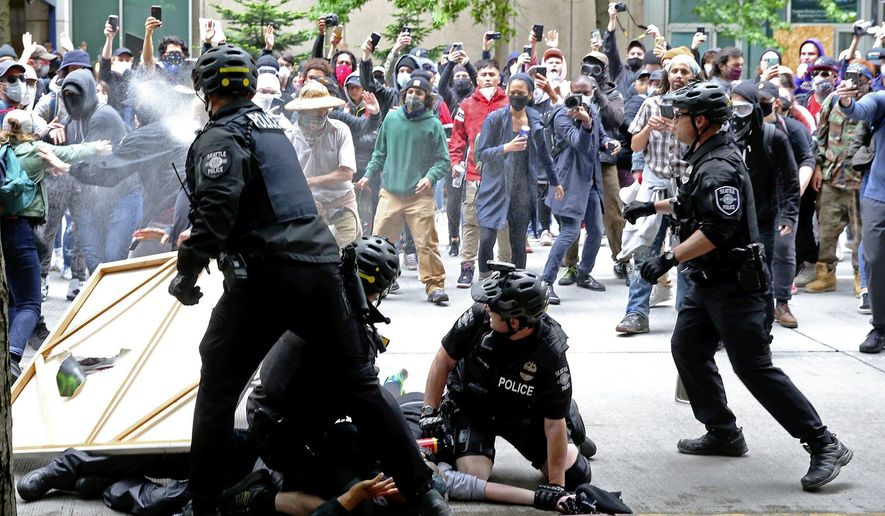 Protesters surrounding police officers making an arrest are pepper sprayed in downtown Seattle, Sunday, May 31, 2020, as demonstrations continue over the death of George Floyd. Floyd died after being restrained by Minneapolis police officers on May 25. (Ken Lambert/The Seattle Times via AP)
