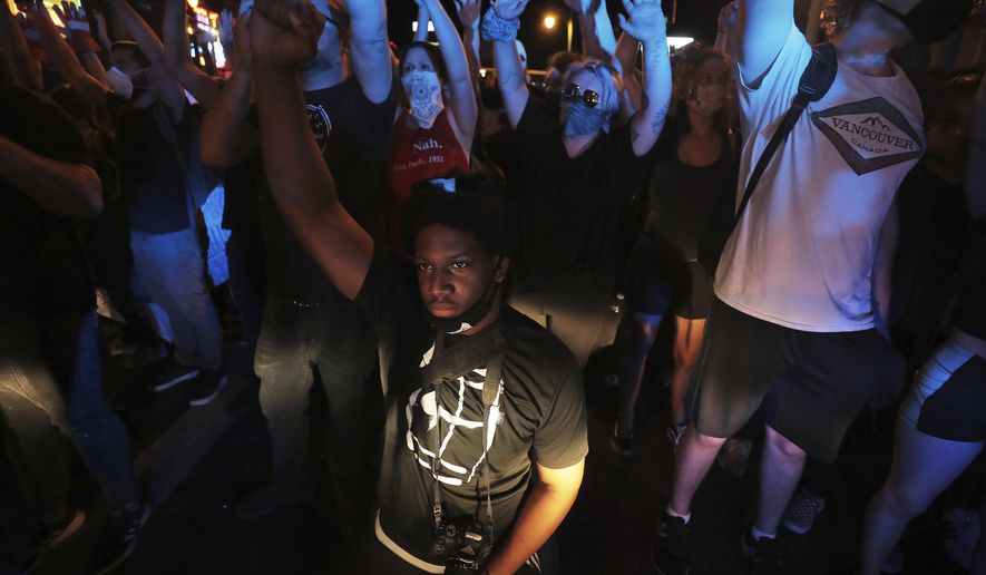 In this May 31, 2020, photo, a protester kneels in front of a line of police near Beale Street in Memphis as they protest the death of George Floyd in Minneapolis police custody May 25, 2020. (Patrick Lantrip/Daily Memphian via AP)