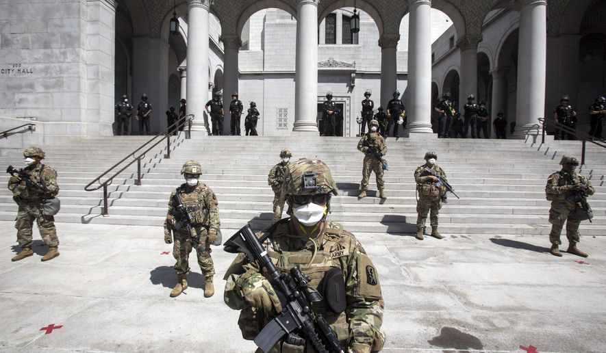 Members of California National Guard stand guard outside the City Hall, Sunday, May 31, 2020, in Los Angeles. The National Guard is patrolling Los Angeles as the city begins cleaning up following a night of violent protests against police brutality. The demonstration Saturday night was sparked by the death of George Floyd, a black man who was killed in police custody in Minneapolis on May 25. (AP Photo/Ringo H.W. Chiu)
