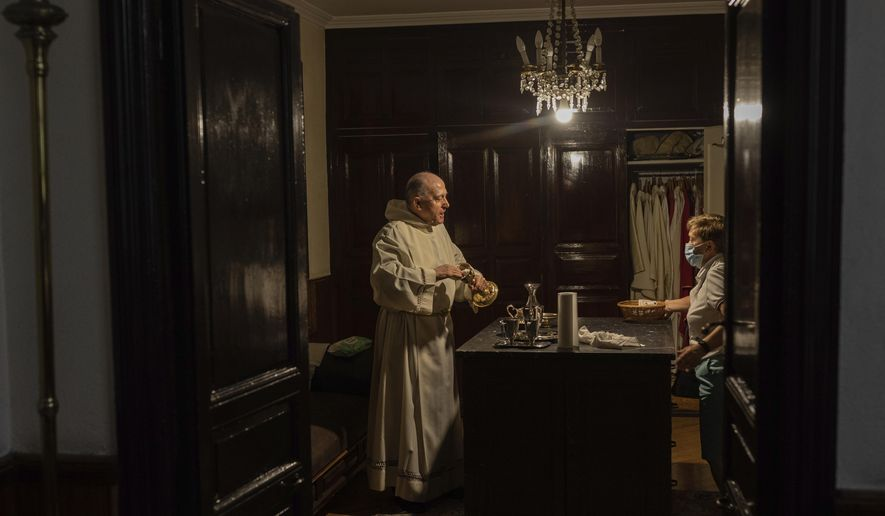 Catholic priest Pedro Luis, left, talks with a church volunteer, wearing face mask protection to prevent the spread of the coronavirus, after a mass at the San Ildefonso church in Madrid, Spain, Sunday, May 31, 2020. (AP Photo/Bernat Armangue)