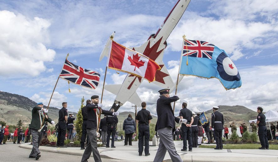 Flags are carried at a tribute ceremony to honour Capt. Jennifer Casey at the Kamloops Airport Thursday May 21, 2020. Capt. Casey, the Snowbirds public affairs officer, died after the Snowbirds jet she was in crashed shortly after takeoff.  (Jeff Bassett/The Canadian Press via AP)