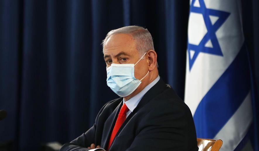 Israeli Prime Minister Benjamin Netanyahu wears a mask as he looks on during the weekly cabinet meeting in Jerusalem Saturday, May 31, 2020. (Ronen Zvulun/Pool Photo via AP)