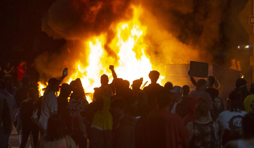 In this May 29, 2020, photo, protesters light a fire to block West 7th Ave. at Jefferson St. in Eugene, Ore. during a protest over the killing of George Floyd in Minneapolis, Minnesota. (Chris Pietsch/The Register-Guard via AP)