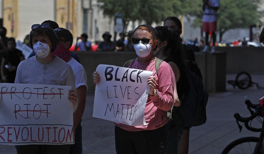 Protesters gather and hold signs in front of Dallas City Hall in downtown Dallas, Saturday, May 30, 2020. Protests across the country have escalated over the death of George Floyd who died after being restrained by Minneapolis police officers on Memorial Day. (AP Photo/LM Otero)