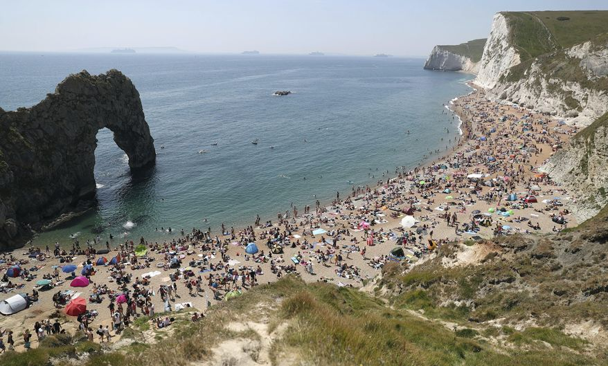 People on the beach at Durdle Door, as the public are being reminded to practice social distancing following the relaxation of coronavirus lockdown restrictions, near Lulworth in Dorset, England, Saturday, May 30, 2020.  (Andrew Matthews/PA via AP)