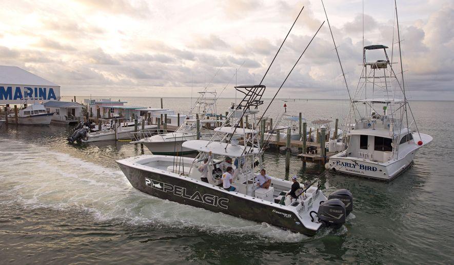 In this photo provided by the Florida Keys News Bureau, Captain Chase Fulton takes guest fishing in the Florida Keys on his chartered sportfishing boat Monday, June 1, 2020, in Islamorada, Fla. (Andy Newman/Florida Keys News Bureau via AP)
