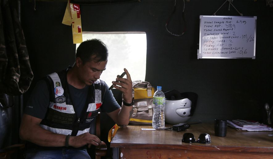 """Arun Saiju of the RNA-16 volunteer group speaks on a phone inside his makeshift shelter during lockdown at a hospital in Bhaktapur, Nepal, Tuesday, May 26, 2020. RNA-16 stands for """"Rescue and Awareness"""" and the 16 kinds of disasters they have prepared to deal with, from Nepal's devastating 2015 earthquake to road accidents. But the unique services of this group of three men and a woman in signature blue vests in the epidemic amount to a much greater sacrifice, said doctors, hospital officials and civic leaders. (AP Photo/Niranjan Shrestha)"""