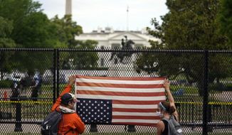 Demonstrators protest the death of George Floyd with an upside-down American flag, Tuesday, June 2, 2020, near the White House in Washington. Floyd died after being restrained by Minneapolis police officers. (AP Photo/Evan Vucci)