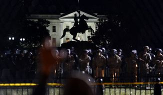 With the White House in the background, a person holds on to the a fence in front of a line of police in Lafayette Park as demonstrators gather to protest the death of George Floyd, Tuesday, June 2, 2020, near the White House in Washington. Floyd died after being restrained by Minneapolis police officers. (AP Photo/Evan Vucci)