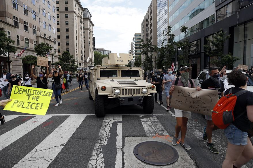 Demonstrators march past a military humvee as they protest the death of George Floyd, Tuesday, June 2, 2020, in Washington. Floyd died after being restrained by Minneapolis police officers. (AP Photo/Alex Brandon)