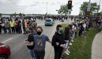 "Protesters block an intersection Monday, June 1, 2020, in Madison, Wis. Several hundred protesters marched through and blocked all six lanes of John Nolan Drive as part of what they say will be a week of action against police brutality and ""white supremacy."" (Steve Apps/Wisconsin State Journal via AP)"