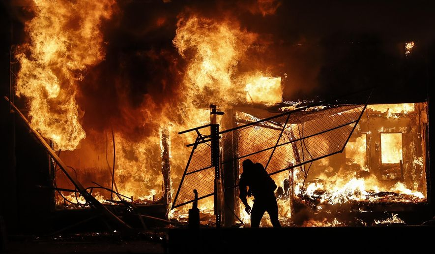 An arsonist adds materials to a fire of a building that once housed a check cashing business, in St. Paul, Minnesota, May 30, 2020. The destruction caused by vandals and looters in cities across the country, who struck as demonstrators took to the streets in reaction to the killing of George Floyd in Minneapolis, has devastated small businesses already reeling from the coronavirus outbreak. (AP Photo/John Minchillo)  ** FILE **