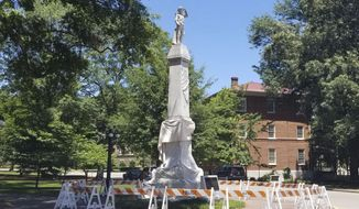 A tarp covers part of a Confederate monument Monday, June 1, 2020, on the University of Mississippi campus in Oxford, Miss. The monument, vandalized Saturday evening, is surrounded by barricades. (Nick Suss/The Clarion-Ledger via AP)