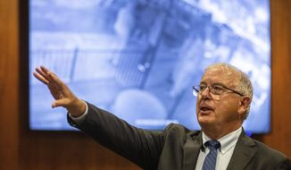 Douglas County Attorney Don Kleine talks Monday, June 1, 2020, in Omaha, Neb., about the video playing on several monitors that shows the fatal shooting of James Scurlock on Saturday. Kleine said that Jake Gardner, who owns two bars near where the shooting happened, fired the fatal shot during a scuffle with protesters outside one of his bars. Kleine said the bar owner said he feared for his life before the shooting. (Chris Machian/Omaha World-Herald via AP)