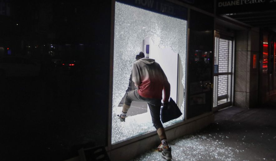 A person enters a store through a broken window Monday, June 1, 2020, in New York. (AP Photo/Frank Franklin II)