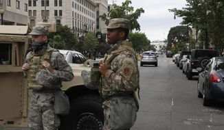 Members of the D.C. National Guard block an intersection on 16th Street as demonstrators gather to protest the death of George Floyd, Tuesday, June 2, 2020, near the White House in Washington. Floyd died after being restrained by Minneapolis police officers. (AP Photo/Jacquelyn Martin) ** FILE **