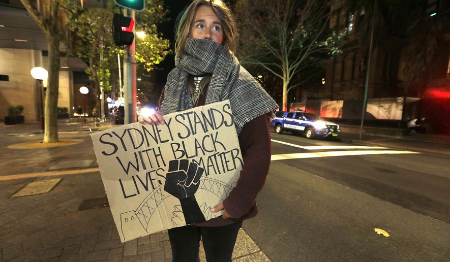 A protester from St. Louis, U.S., who gave her name as Merinda, carries a handmade sign as demonstrators gather in Sydney, Tuesday, June 2, 2020, to support the cause of U.S. protests over the death of George Floyd and urged their own governments to address racism and police violence. Floyd died last week after he was pinned to the pavement by a white police officer who put his knee on the handcuffed black man's neck until he stopped breathing. (AP Photo/Rick Rycroft)
