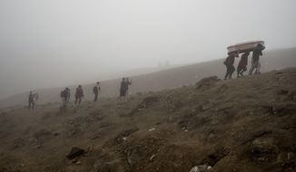 Cemetery workers carry the remains of Flavio Juarez, 50, who died of COVID-19, up the hill at the Nueva Esperanza cemetery on the outskirts of Lima, Peru, Tuesday, May 26, 2020. (AP Photo/Rodrigo Abd)