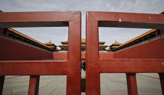 In this Thursday, March 12, 2020, file photo, an entrance gate is closed at the usually crowded Forbidden City in Beijing, due to the COVID-19 coronavirus outbreak. (AP Photo/Andy Wong)