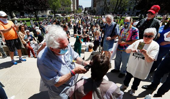 Barber Karl Manke clips people's hair at the top of the Michigan state capitol steps in Lansing last month. Mr. Manke is taking his lawsuit to continue to cut hair during the pandemic to the state Supreme Court. (Associated Press)
