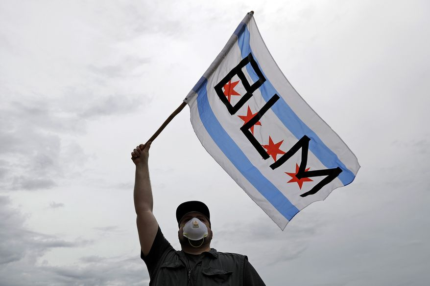 A protester waves a banner emblazoned with the acronym BLM for Black Lives Matter, outside City Hall during a protest over the death of George Floyd, on Wednesday, June 3, 2020, in Batavia, Ill. Floyd, an African American, died on May 25 after a white Minneapolis police officer pressed a knee into his neck for several minutes even after he stopped moving and pleading for air. (AP Photo/Nam Y. Huh)