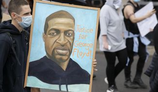 A protester holding a banner showing George Floyd marches as they take part in a demonstration on Wednesday, June 3, 2020, in London, over the death of George Floyd, a black man who died after being restrained by Minneapolis police officers on May 25. Protests have taken place across America and internationally, after a white Minneapolis police officer pressed his knee against Floyd's neck while the handcuffed black man called out that he couldn't breathe. The officer, Derek Chauvin, has been fired and charged with murder. (AP Photo/Kirsty Wigglesworth)