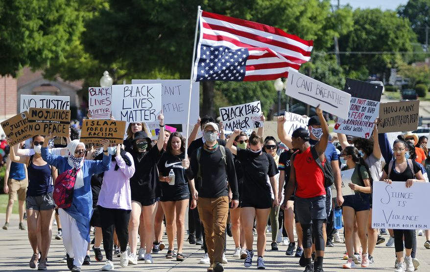 Protesters march beside the Plano Police Department at a protest organized by Our Revolution Texas, Wednesday, June 3, 2020, in Plano, Texas. (Stewart F. House/The Dallas Morning News via AP)  ** FILE **