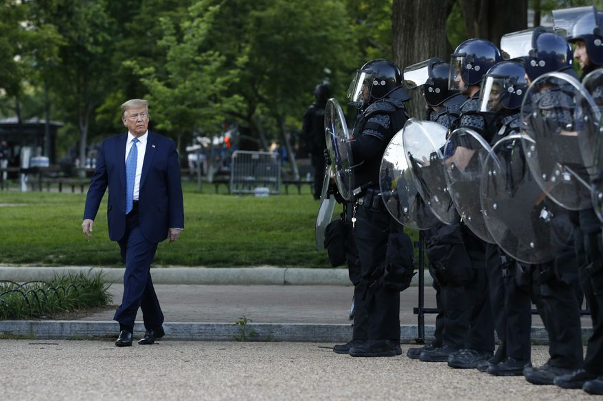 In this Monday, June 1, 2020, file photo, President Donald Trump walks past police in Lafayette Park after visiting outside St. John's Church across from the White House in Washington. Part of the church was set on fire during protests on Sunday night. (AP Photo/Patrick Semansky, File)