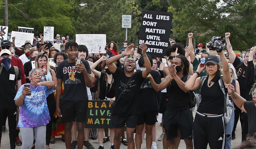 Demonstrators chant outside the Norman Police Department on Tuesday, June 2, 2020, in Norman, Okla., during a protest over the death of George Floyd, who died after being restrained by Minneapolis police officers May 25. (AP Photo/Sue Ogrocki)