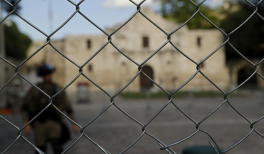 A member of the National Guard and the Alamo are seen behind a newly erected protective fence in San Antonio, Wednesday, June 3, 2020. The grounds are being protected with the fence and a curfew as a precautionary measure to minimize the possibility of civil disturbance and damage to sensitive structures as protests have broken out over the death of George Floyd.  Demonstrators took to the streets across the United States again Wednesday to protest the death of Floyd, a black man who was killed in police custody in Minneapolis on May 25. (AP Photo/Eric Gay)