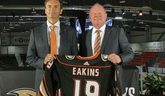 FILE - In this  Monday, June 17, 2019 file photo, Anaheim Ducks head coach Dallas Eakins, left, and general manager Bob Murray pose with a jersey at Great Park Ice in Irvine, Calif. General manager Bob Murray saw intermittent signs of progress from his young Ducks players and first-year coach Dallas Eakins while Anaheim missed the playoffs for the second consecutive season. (AP Photo/Greg Beacham, File)