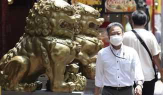 A man wearing a face mask to protect against the spread of the new coronavirus walks through China Town in Yokohama, near Tokyo, Wednesday, June 3, 2020. A coronavirus state of emergency was lifted, ending the restrictions nationwide as businesses began to reopen. (AP Photo/Koji Sasahara)